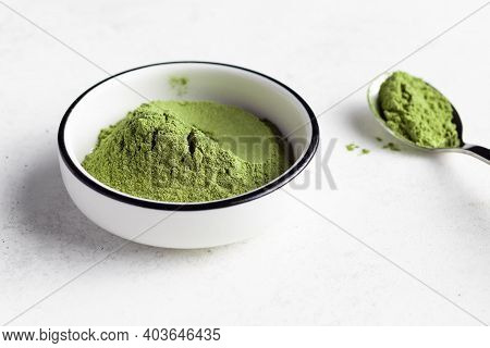 Green Superfood Powder In White Bowl. Powder Mix From Wheat Grass, Barley Grass, Chlorella, Spirulin