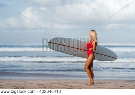 Surf Woman With Long Blonde Hair Go To Ocean. Female Holding Surfboard Ready To Surf. Bali Island, I