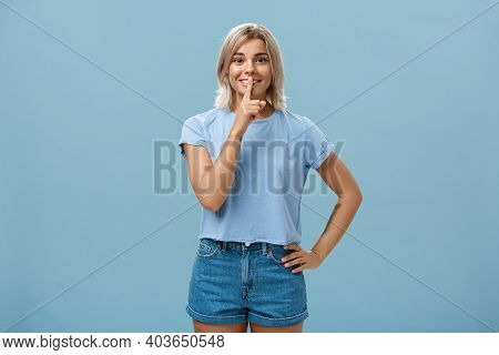 Studio Shot Of Dreamy Optimistic Good-looking Fair-haired Female In Denim Shorts Saying Shh Showing