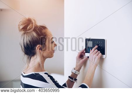 Blonde Woman Entering Code On Home Security Alarm Keypad.