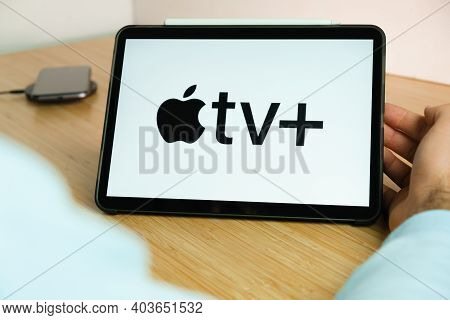 Apple Tv Logo On The Screen Of The Ipad Tablet With Charging Smart Phone On The Wireless Charger On