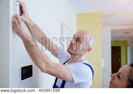 Handsome Male Alarm Fitter Mounts The Alarm. The Woman Is Learning How To Use It.