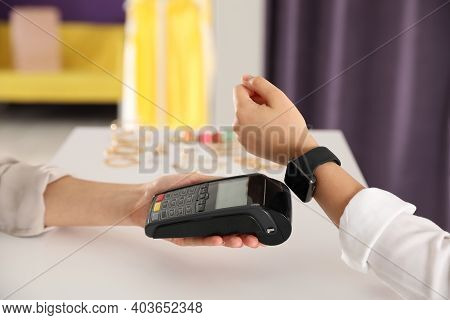 Woman Using Terminal For Contactless Payment With Smart Watch In Shop, Closeup