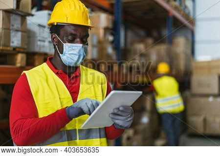 Black Man Working In Warehouse Doing Inventory Using Digital Tablet And Loading Delivery Boxes Plan