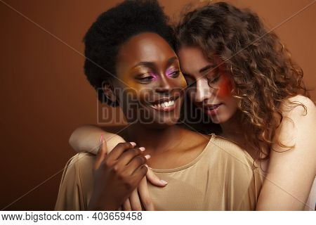 Two Pretty Girls African And Caucasian Blond Posing Cheerful Together On Brown Background, Ethnicity