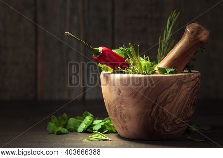 Wooden Mortar With Pepper And Herbs On An Old Wooden Table. In Mortar Red Pepper, Rosemary, Coriande