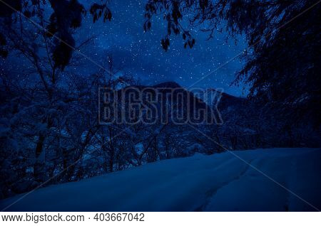 Mountain Road Through The Snowy Forest On A Full Moon Night. Scenic Night Winter Landscape Of Dark B