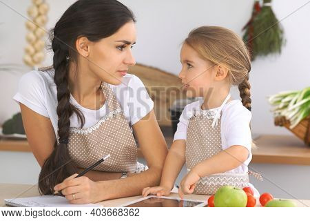 Happy Family In The Kitchen. Mother And Child Daughter Make Menue For Cooking Tasty Breakfest In The