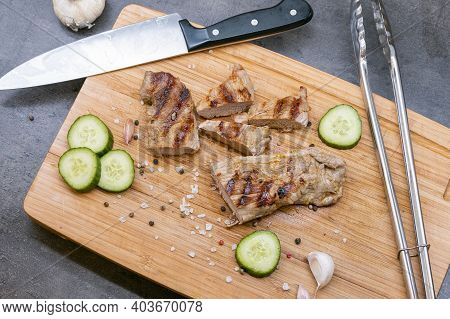 Grilled Pork Tenderloin Cut On A Wooden Board. Grilled Meat With Cucumber, Garlic And Salt. Knife An