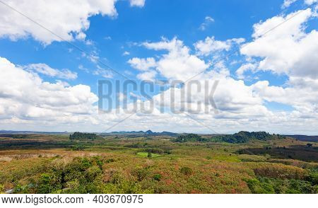 White Clouds In Blue Sky Over Green Mountains Covered With Rainforests Trees.