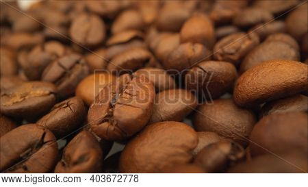 Production Of Grain Coffee Close Up. Freshly Roasted Coffee Beans In A Coffee Maker. Roasted Coffee