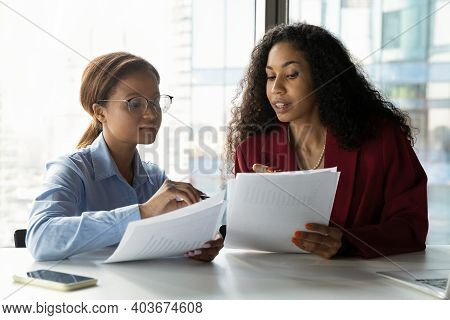 Multiracial Colleagues Consider Company Paperwork At Meeting
