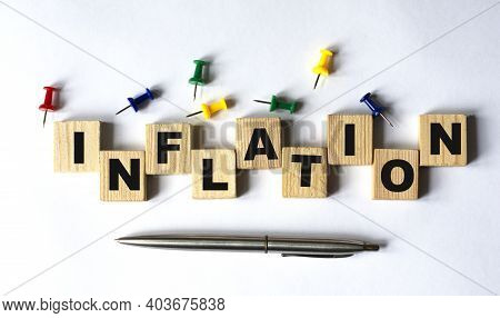 Inflation - Word On Wooden Cubes With Stationery Buttons, Pen On White Background. Business Concept