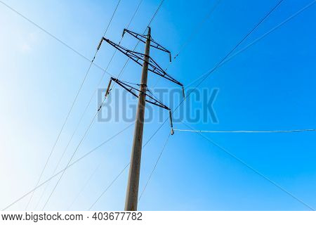 High-voltage Transmission Line With Concrete Supports On The Background Of Blue Sky