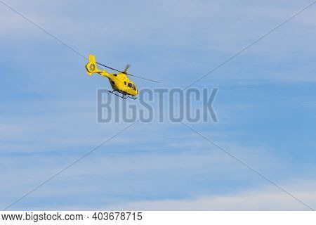 Yellow Helicopter Flying Against The Blue Sky