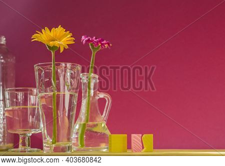 Gerberas In Glass Bottles On A Pink Background. A Floral Minimalistic Concept In A Modern Interior W