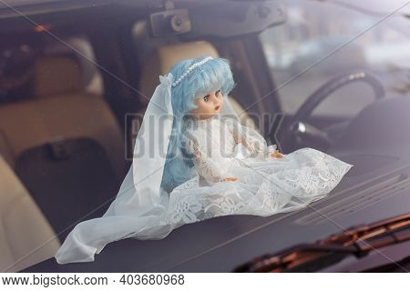 Children's Doll At A Wedding. A Doll In A Wedding Dress On The Hood Of A Car.