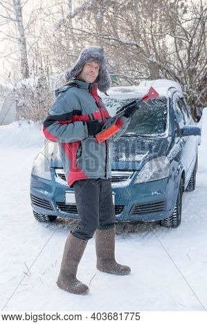 Cheerful, Cheerful, A Man In Huge Felt Boots And A Fur Hat Stands By A Car With A Snow Brush. Preten