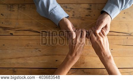 Compassionate Middle Aged Man Holding Wrinkled Hands Of Elderly Woman.