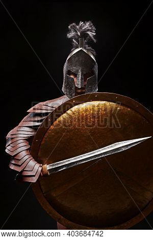 Gladiator With Sword And Armor On A Black Background. A Warrior In Gladiatorial Armor And A Helmet H