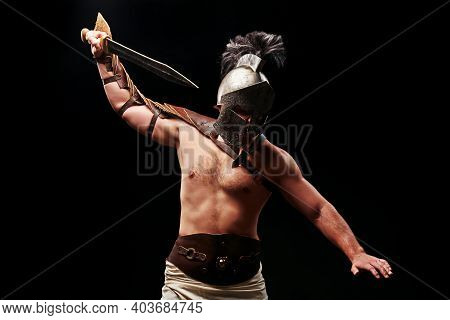 Gladiator With Sword And Armor On A Black Background. A Warrior In Gladiatorial Armor And A Helmet C