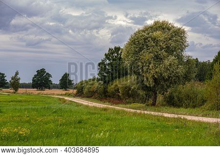 A Country Road Winds Through Meadows And Fields Against A Cloudy Sky. Rural Landscape.