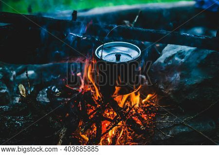 Kettle In Soot Hanging Over Fire. Cooking Food At Fire In Wild. Beautiful Firewoods Burn In Bonfire