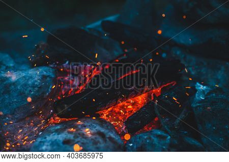 Vivid Smoldered Firewoods Burned In Fire Closeup. Atmospheric Background With Orange Flame Of Campfi