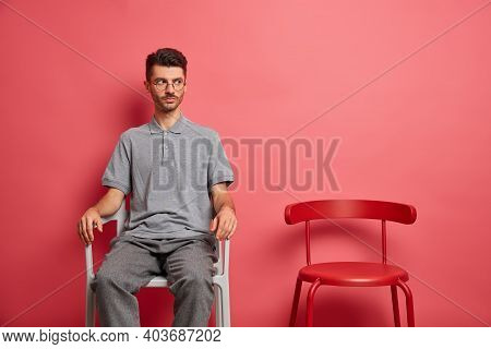 Serious Man With Stubble Dressed In Casual Clothes Poses On Chair Looks Pensively Somewhere Isolated