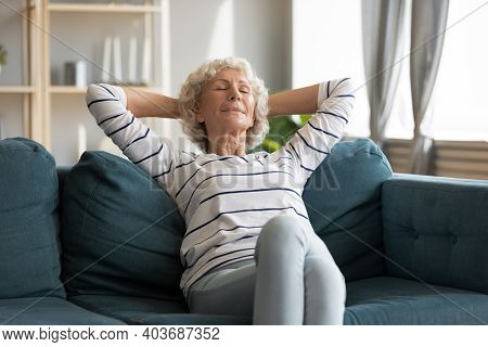Peaceful Calm Retired Woman Relaxing Om Comfortable Sofa.