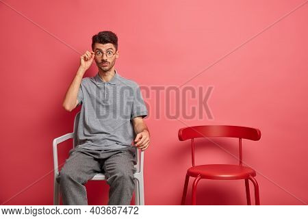 Surprised Young Man With Stubble Stares Through Spectacles Poses On Chair Hears Astonishing News Dre