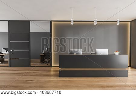 Black And Wooden Reception Room With Two Computers, Conference Office Room. Black Wall With Backligh