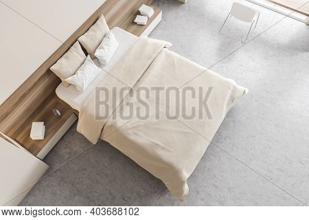 Top View Of Wooden Light Bedroom, Bed With Beige Pillows And Linens, Books And Chair. Beige And Wood