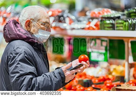 Old Senior European Man Wearing Protective Facial Mask And Looking At Tomato With A Mobile Phone In
