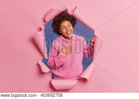 Happy Sincere Young African American Woman Giggles Positively Feels Very Glad Keeps Hand On Chest We