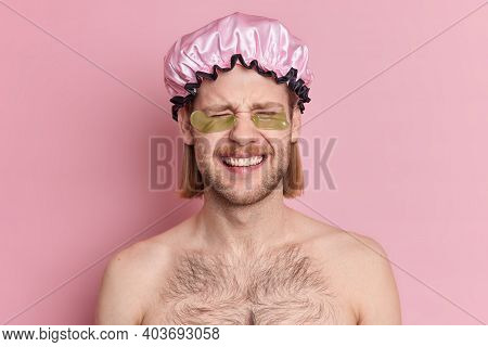 Funny Shirtless Young Man Wears Bath Hat And Hydrogel Patches Under Eyes Enjoys Beauty Treatments Af