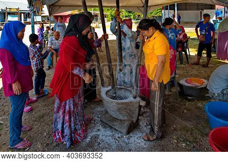 Semporna.malaysia. November 30, 2018. Women From A Gypsy Fishing Village Grind Rice Flour In A Large