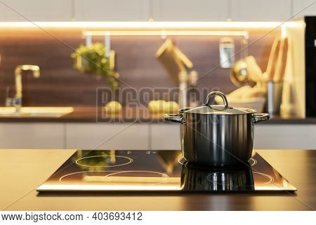 Cooking Homemade Food Concept. Metal Saucepan On Electric Stove Against Blurred Contemporary Interio