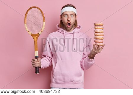 Bearded Shocked Hipster Wears Sport Outfit Holds Tennis Racket And Pile Of Sweet Doughnuts Gazes Sur