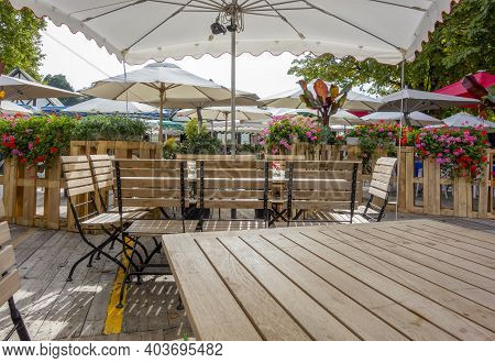 Idyllic Beer Garden Scenery With Seats, Tables And Sunshade