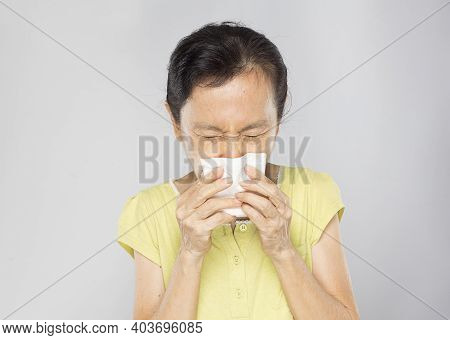 Old Asian Woman Put Hand Over Her Mouth To Sneeze