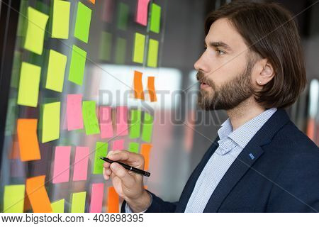 Focused Young Male Project Manager Analyzing Working Processes.