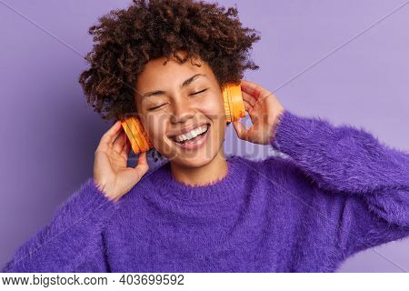Carefree Optimistic Woman With Afro Hair Smiles Broadly Feels Very Glad Listens Favorite Music Track