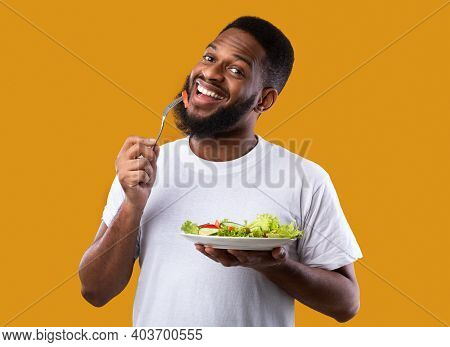Cheerful Black Guy Eating Salad Posing Holding Plate And Fork Enjoying Healthy Meal Standing Over Ye