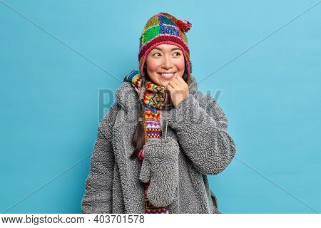 Glad Asian Woman Wears Knitted Hat Scarf And Grey Coat From Natural Fur Smiles Positively Has Good M