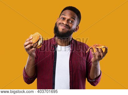 Smiling African Man Holding Burger And Slice Of Pizza Posing Standing In Studio Over Yellow Backgrou