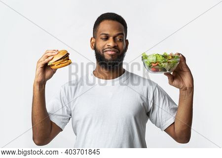 Food Choice. Hungry African Guy Holding Burger And Vegetable Salad Choosing Diet Standing On White S