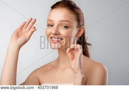 Shirtless Young Woman Flossing Cleaning Teeth Using Dental Thread Smiling To Camera Posing In Studio