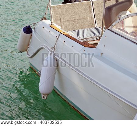 Small Ship Fenders Hanging Above Pleasure Yacht Hull