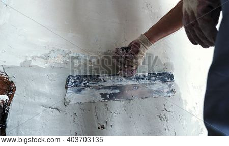The Builder Evens Out The Walls Of The Room With Elastic Plaster And A Wide Spatula, The Working Too